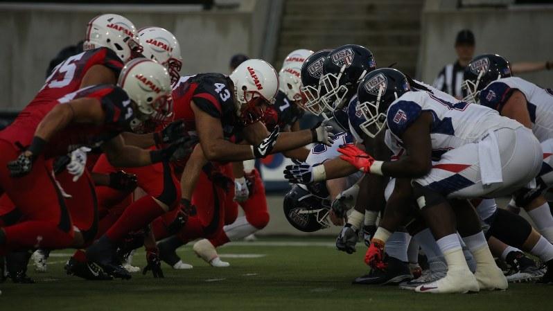 アメリカンフットボール世界選手権の日本対米国戦で、激しくぶつかり合う選手たち=2015年7月12日、米国オハイオ州カントンで小座野容斉撮影