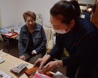 ヘルパーの中野浩子さん(右)に買い物を頼む一之瀬直枝さん。心臓病でひざも悪く買い物途中で動けなくなったこともある。左手首は骨折したままだ=東京都国立市で