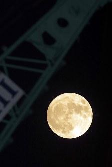 巨大なクレーンの先に浮かぶスーパームーン=岩手県釜石市で2016年11月14日午後6時6分、喜屋武真之介撮影