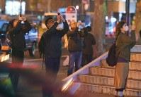 さっぽろテレビ塔のそばに輝くスーパームーンを撮影する人たち=札幌市中央区で2016年11月14日午後8時54分、手塚耕一郎撮影