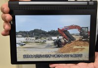 A scene from reconstruction work is displayed on a tablet screen while using the