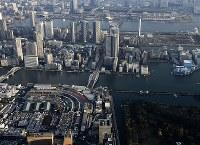 来年冬以降に豊洲市場(上)への移転可能時期が示された築地市場(手前)。両市場の間を走る道路は環状2号線(中央)=東京都内で2016年11月18日午後3時27分、本社ヘリから