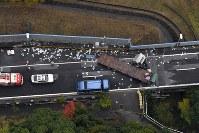大型車両が道路を塞ぐ事故現場=神戸市須磨区で2016年11月19日午前11時2分、本社ヘリから三浦博之撮影