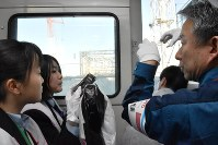 Students from Fukushima High School ride a bus and are told by Tokyo Electric Power Co. executive Yoshiyuki Ishizaki, right, about the Fukushima No. 1 Nuclear Power Plant's No. 1 reactor, which just had a cover removed from its building, in Okuma, Fukushima Prefecture, on Nov. 18, 2016. (Mainichi)