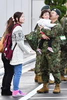 An engineering corps member of the Self-Defense Forces, right, says goodbye to people who came to see him off, at Aomori Airport on Nov. 20, 2016. (Mainichi)