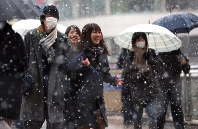 Students head to school in snowy conditions in Hachioji, Tokyo, on Nov. 24, 2016. (Mainichi)
