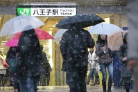 People walk through the snow in front of JR Hachioji Station in Hachioji, Tokyo, on Nov. 24, 2016. (Mainichi)