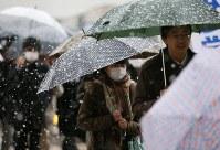 雪が降る中で通勤通学する人たち=東京都八王子市で2016年11月24日午前7時5分、宮武祐希撮影