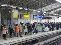 雪の降る中、列車の到着を待つ人たち=東京都大田区の京浜急行糀谷駅で2016年11月24日午前10時38分、米田堅持撮影