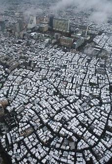 東京都心の市街地にうっすらと積もった雪。中央奥はJR中野駅=東京都中野区で2016年11月24日午後4時35分、本社ヘリから小川昌宏撮影