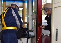料金所の収受員を拳銃で脅し現金を奪う強盗(右)