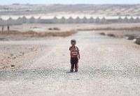乾いた大地が広がるアズラック難民キャンプで暮らす男の子。約3万6000人が暮らすアズラックでは58%が18歳未満の子どもだ。後方には居住用のコンテナが建ち並ぶ=ヨルダン・ザルカ県で2016年9月29日、久保玲撮影