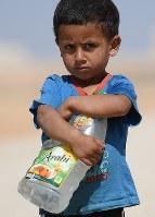 水が入ったペットボトルを抱える3歳の男の子。各戸に水道が引かれていないため、水道がある広場と居住用のコンテナを往復するのが日課になっている=ヨルダン・ザルカ県のアズラック難民キャンプで2016年10月4日、久保玲撮影