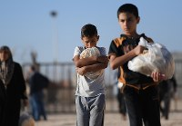毎朝6時から1人4枚ずつ配給されるパンを抱えて歩く男の子=ヨルダン・マフラク県のザータリ難民キャンプで2016年9月28日、久保玲撮影