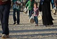 配られたパンを持って自宅に戻る女の子。配給の列には大勢の子どもたちが並んでいる=ヨルダン・マフラク県のザータリ難民キャンプで2016年9月28日、久保玲撮影