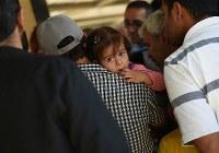 外出許可を求め、父親に抱えられながらキャンプを管轄する警察の窓口に並ぶ女の子。外出がすぐに認められることはほとんどない=ヨルダン・ザルカ県のアズラック難民キャンプで2016年10月3日、久保玲撮影