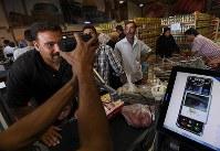スーパーマーケットで虹彩を読み取る装置を使って精算する人たち。虹彩認識の仕組みを使った最先端のシステムが導入されている=ヨルダン・ザルカ県のアズラック難民キャンプで2016年10月3日、久保玲撮影