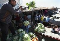 キャンプ外から仕入れた野菜を受け取る人たち。「シャンゼリゼ通り」には青果店も軒を連ねる=ヨルダン・マフラク県のザータリ難民キャンプで2016年10月2日、久保玲撮影