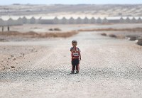 A little boy stands in the road at Azraq refugee camp in Jordan in September 2016. There are about 36,000 Syrians living in the camp, and some 58 percent of them are under 18 years old. Behind the boy in the distance can be seen rows of shipping containers that serve as the refugees' homes. (Mainichi)