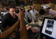 A customer at the Azraq refugee camp supermarket looks into an iris scanner, in Jordan in October 2016. The scan is part of a high-tech payment system. (Mainichi)