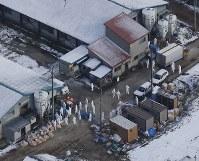高病原性鳥インフルエンザの疑いが濃厚であることがわかった食用のアヒルが飼育されていた農場で作業をする作業員ら=青森市で2016年11月29日午前10時35分、本社機「希望」から