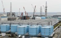 In the background, from left, the No. 1, 2, 3, and 4 reactor buildings of the Fukushima No. 1 Nuclear Power Plant are seen, in Okuma, Fukushima Prefecture, on Oct. 31, 2016. In front are tanks used to store contaminated water. (Mainichi)