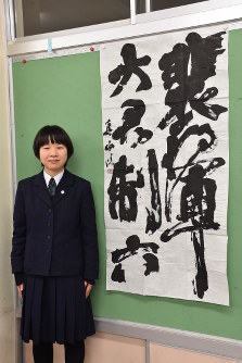 作品の隣に立つ渡辺真由さん=新潟市中央区上所1の新潟南高で