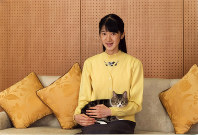 Princess Aiko is seen with her cat Seven at their residence in Tokyo's Minato Ward in this file photo taken on Nov. 23, 2016. (Courtesy of the Imperial Household Agency)