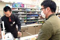 コンビニ店員(左)に現金を要求する犯人役の警察官=鳥取市で、園部仁史撮影
