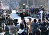 最終運行日を迎え、大勢の鉄道ファンらが待ち構える中で、増毛駅に到着する留萌線の車両=北海道増毛町で2016年12月4日午後1時、手塚耕一郎撮影