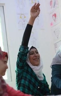 教師の質問に手を挙げるドハ・ムハンマドさん(15)。2年以上前から学校に通っていなかったが、今年サポートスクールに通い始めた。「私は絶対にシリアのことを忘れない。世界中の人にシリアのことを知ってほしい」。将来ジャーナリストになって記事を書いてみたい=ヨルダン・ザルカで2016年10月10日、久保玲撮影