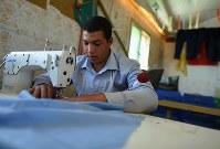 ザータリ難民キャンプの職業訓練学校でミシンを扱うアブダラ・カシャールフェさん(15)。病死した父に代わり農作業や荷物運びで家族5人を支える。仕立てや縫製を学び、学校に行けず農場で働く自分の未来が開けた気がした。「キャンプで店を開きたい。何でも作れるテーラーになりたい」=ヨルダン・マフラク県で2016年9月28日、久保玲撮影