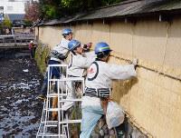 土塀に薦を取り付ける職人たち=金沢市の長町武家屋敷跡で、道岡美波撮影