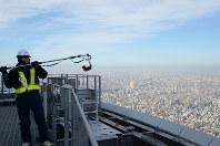 地上375メートルの天望デッキ屋上でコの字形ブラシを実演するスカイツリー関係者