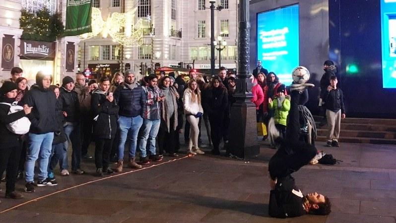 ショッピング街では、通行人が足を止めて大道芸人のパフォーマンスにくぎづけ=英ロンドンで2016年11月、三沢耕平撮影