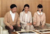Crown Prince Naruhito, Crown Princess Masako and their daughter Princess Aiko look at photos of the Nagano Prefecture area of Kamikochi following a visit in August this year. (Photo courtesy of the Imperial Household Agency)