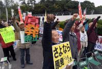 川内原発のゲート前で1号機運転再開への動きに抗議のシュプレヒコールを上げる人たち=津村豊和撮影