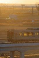 内陸に移された区間を走るJR常磐線の車両。津波の被害を受けた沿岸部は荒れ地が目立っていた=宮城県山元町で2016年12月10日午前7時2分、喜屋武真之介撮影
