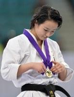 女子形で優勝し、表彰式でメダルを見る清水希容=日本武道館で2016年12月11日、猪飼健史撮影