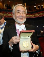 Yoshinori Ohsumi shows off his medal for his prize in physiology or medicine after the Nobel Prize ceremony at a concert hall in Stockholm on Dec. 10, 2016. (Pool photo)