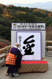 「今年の漢字」に選ばれた「金」を揮毫する清水寺の森清範貫主=京都市東山区で2016年12月12日午後、小松雄介撮影