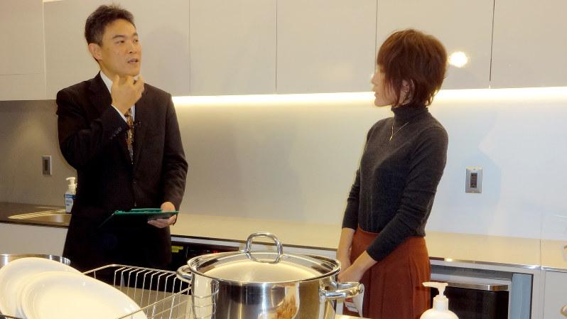 一般的な住宅を模した会場で、母親たちにキッチン周りでの感染症対策について説明する済生会横浜市東部病院の十河剛医師(左)=東京都千代田区で2016年11月28日、鈴木敬子撮影