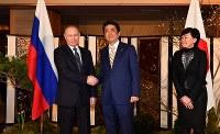 ロシアのプーチン大統領(左)を出迎える安倍首相夫妻=山口県長門市の大谷山荘で2016年12月15日午後6時6分、代表撮影