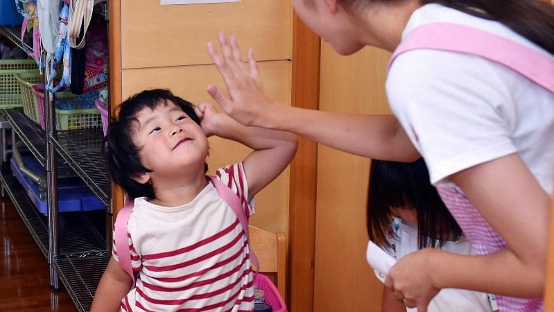保育園の先生にバイバイする子供=関口純撮影