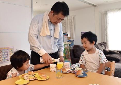 朝食を準備して子供に食べさせるお父さん=関口純撮影