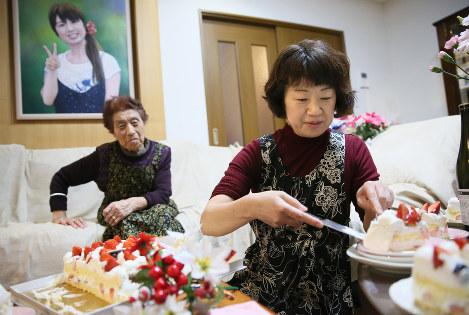12月10日、絵美さんの誕生日会でケーキを切る成田博美さん(右)。左は祖母の千代子さん(84)。左上は絵美さんの肖像画=宮城県石巻市で2016年、佐々木順一撮影