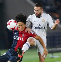 Real Madrid's Daniel Carvajal, right, and the Kashima Antlers' Mu Kanazaki battle for the ball at Nissan Stadium in Yokohama on Dec. 18, 2016. (Mainichi)