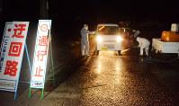発生農場付近を通る軽ワゴン車に消毒液を吹き付ける白い防護服姿の作業員たち=宮崎県川南町で2016年12月19日午後7時34分、尾形有菜撮影
