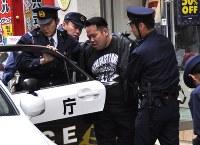 強盗訓練で犯人役をパトカーに乗せる原宿署員ら=渋谷区神宮前で