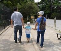 障害基礎年金を昨年末に打ち切られた血友病の男性(左端)。ひざ関節に痛みがあり歩行に困難が伴う。男児(5)と妻(右端)との一家3人の生活は苦しい=関東地方で